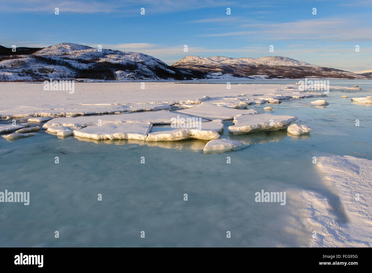 Snow and ice on the shore of a fjord in northern Norway between Tromsø and Alta, 69º north - Stock Image