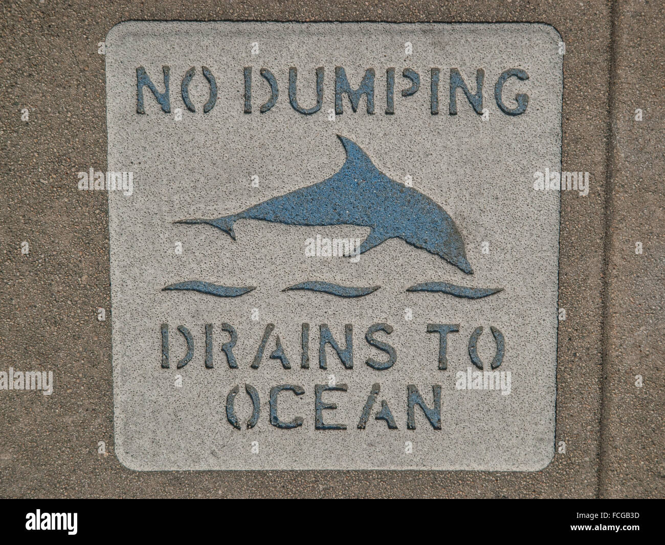 Sign on sidewalk that says No Dumping Drains to Ocean with a picture of a dolphin in Los Angeles California. - Stock Image