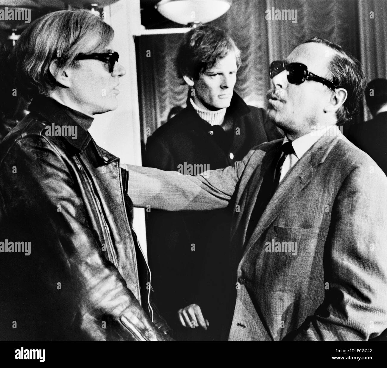 Artist Andy Warhol (left) and playwright Tennessee Williams (right) with film director Paul Morrissey in the background), - Stock Image