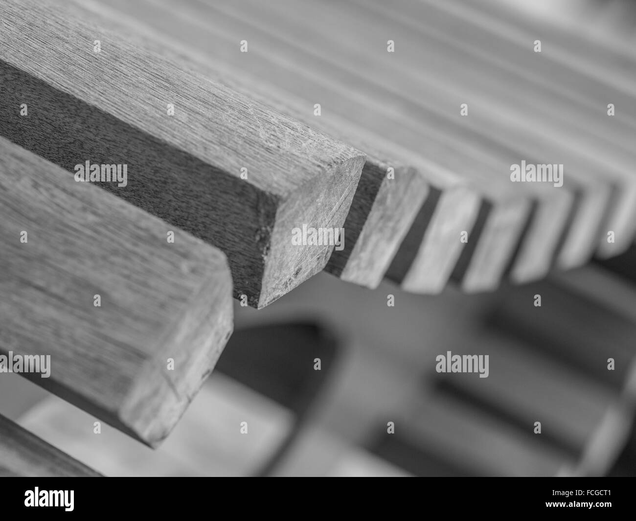 Close up of curved wooden bench in black and white. - Stock Image