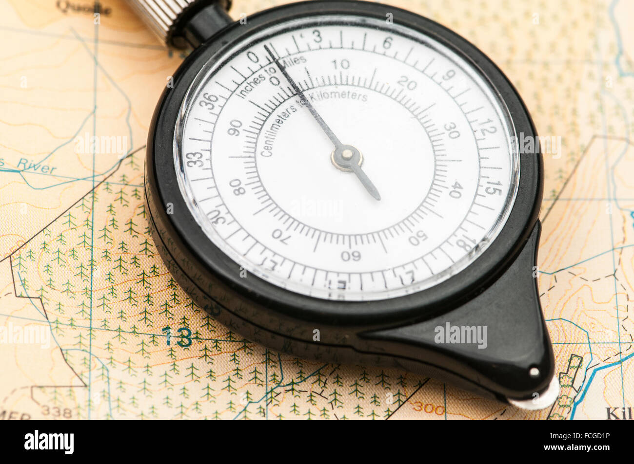 Map wheel on a map, used for measuring distances with different scales. - Stock Image