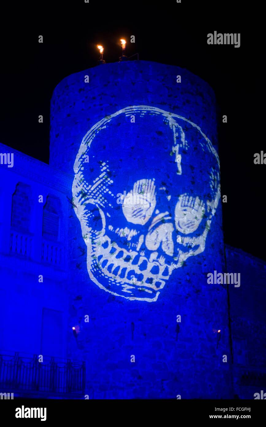 Light projection of a skull over medieval city as part of the feast setup. - Stock Image