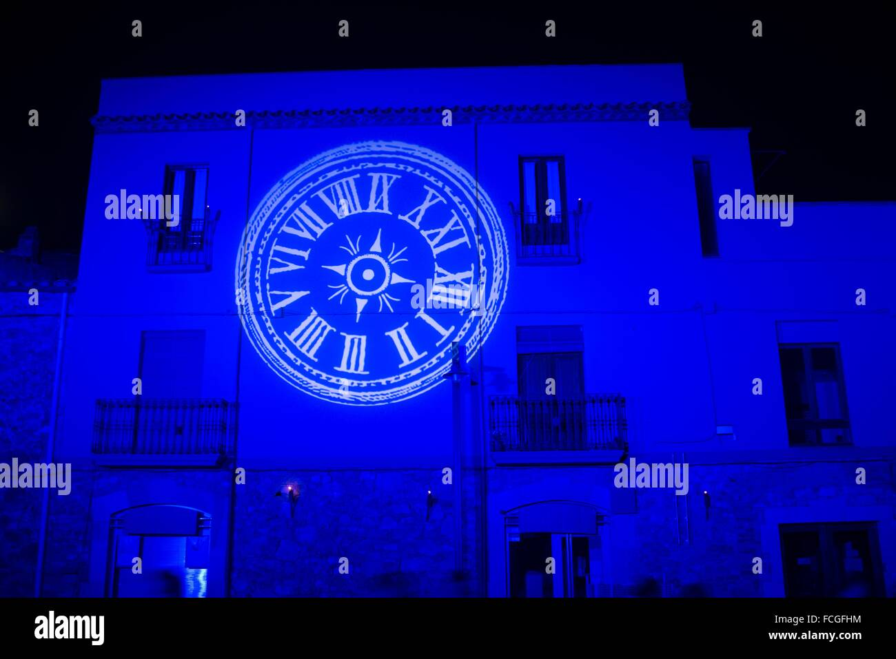 Light projection of a watchless clock over medieval city as part of the feast setup. - Stock Image
