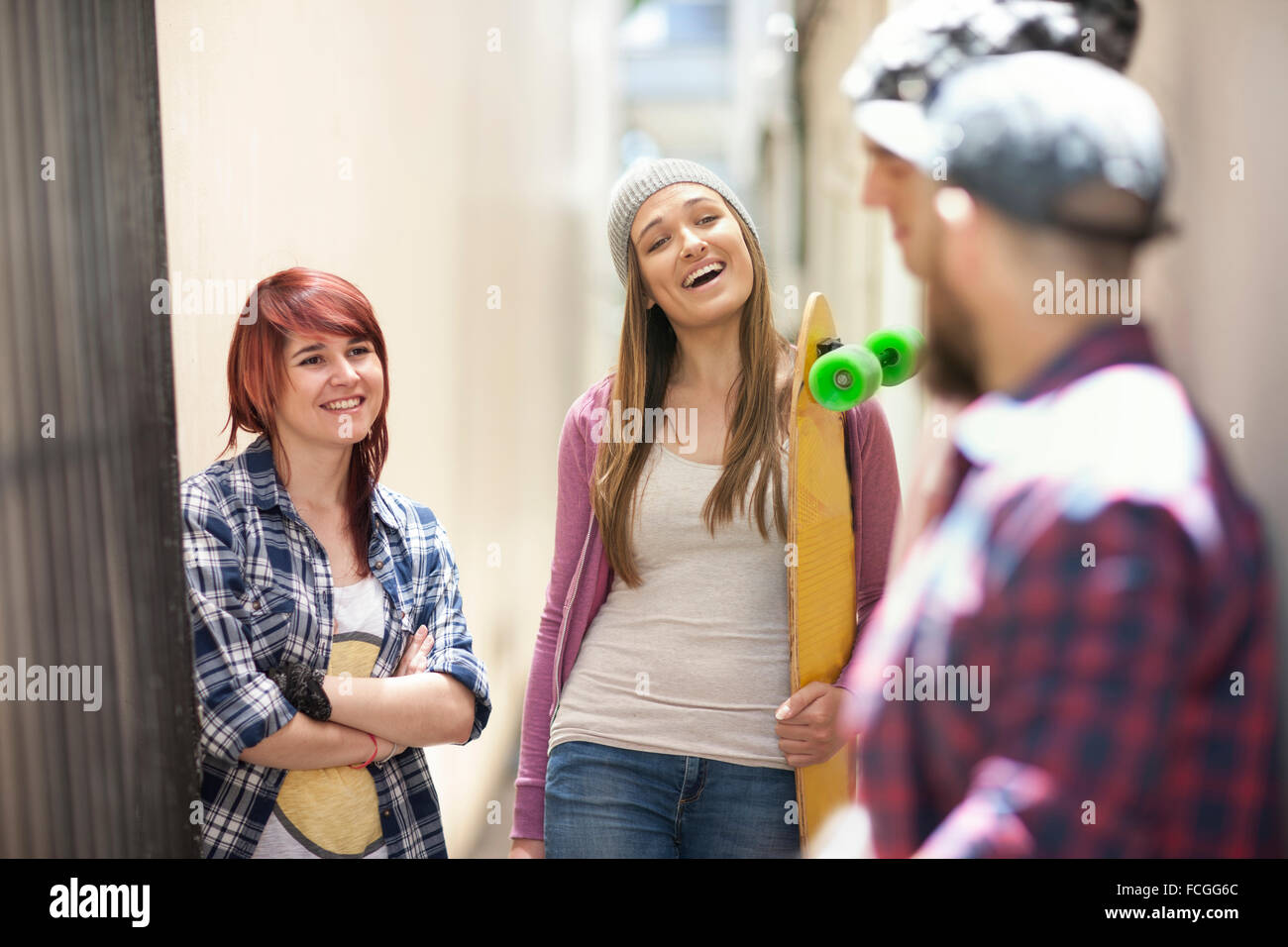 Friends   skateboard talking in a passageway - Stock Image