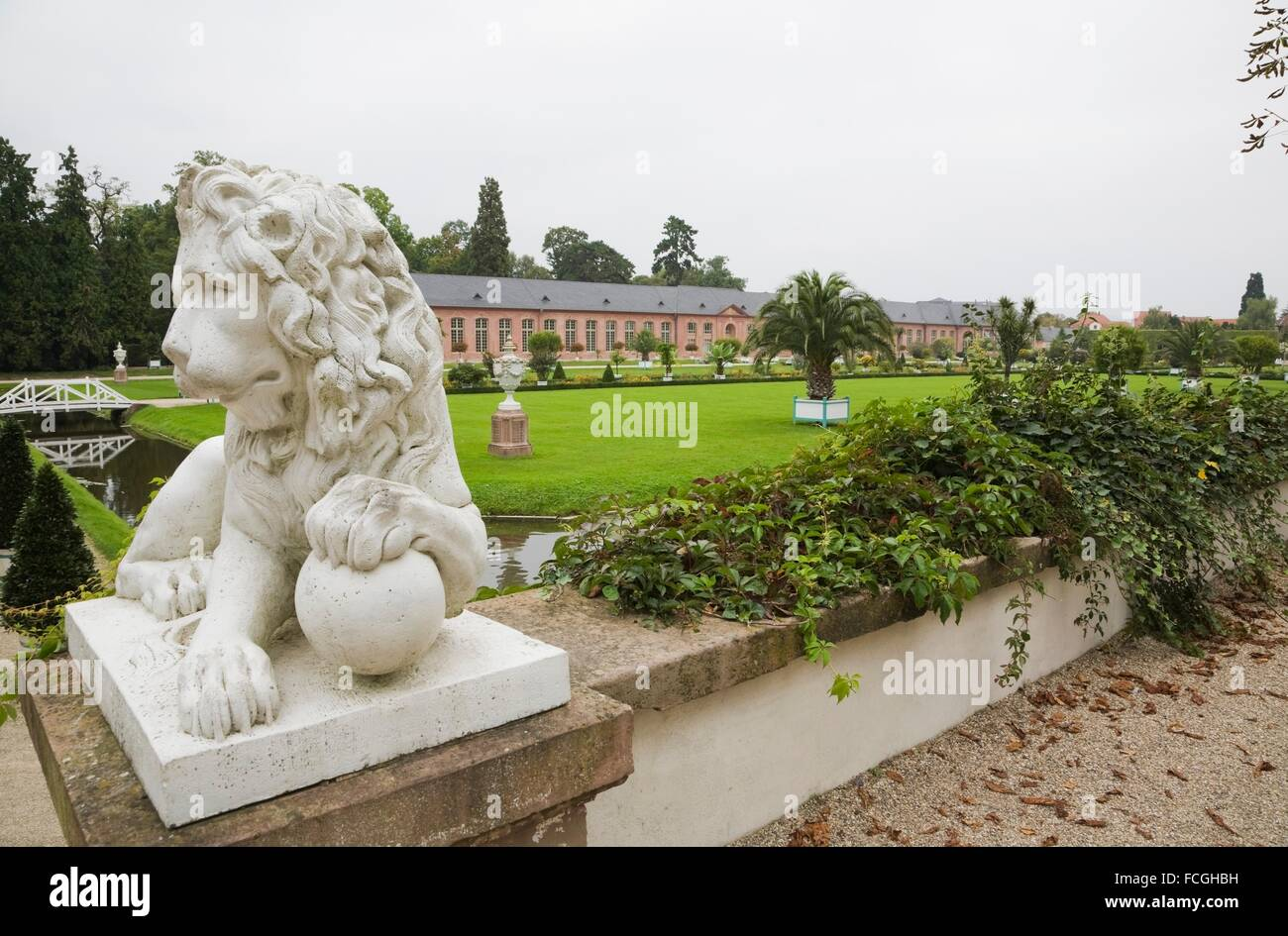 Lion sculpture and new orangery on the Schwetzingen palace grounds in late summer, Schwetzingen, Germany. - Stock Image