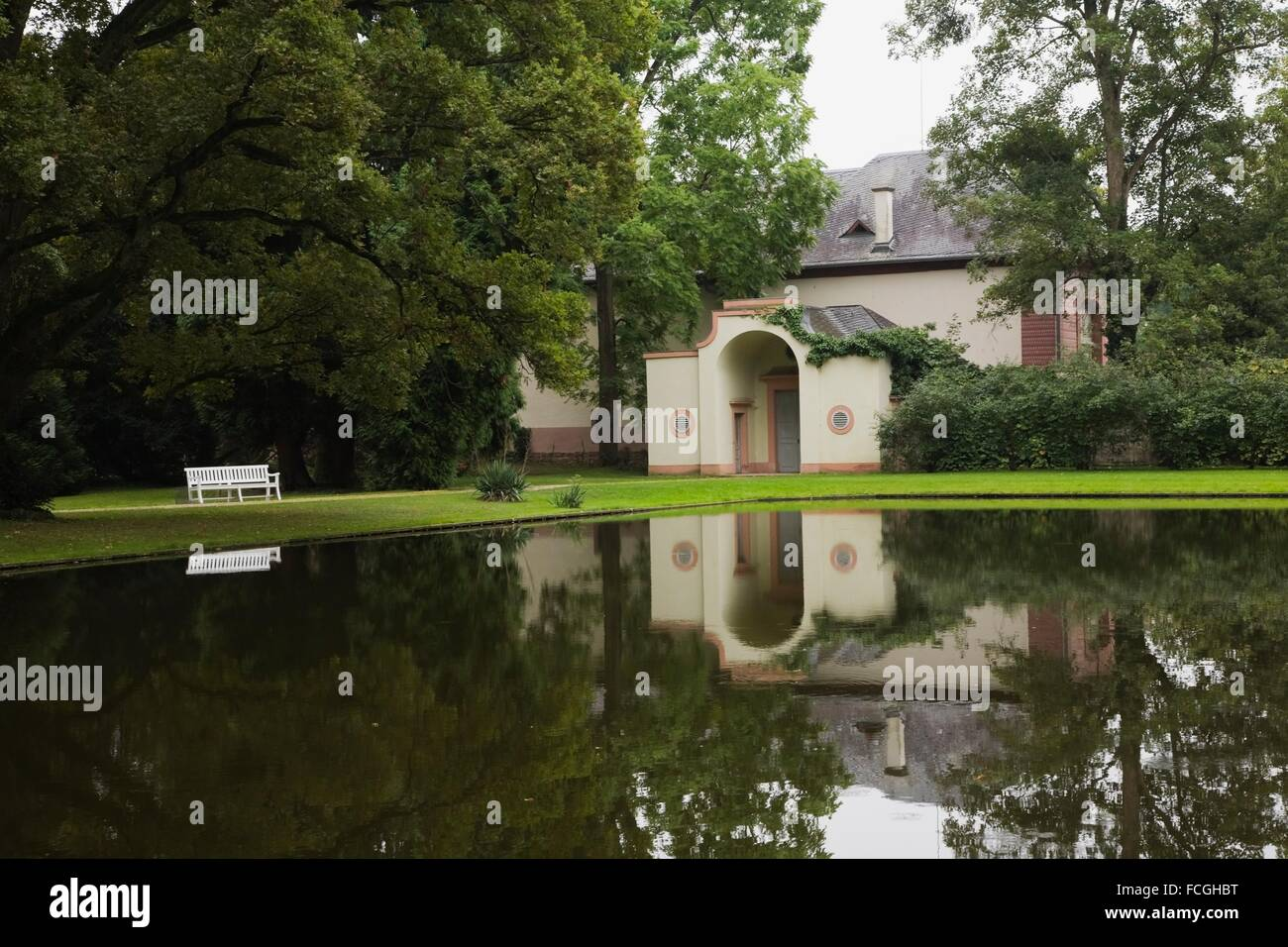 Baroque architectural style building reflected in the water canal in the Schwetzingen palace garden in late summer, - Stock Image
