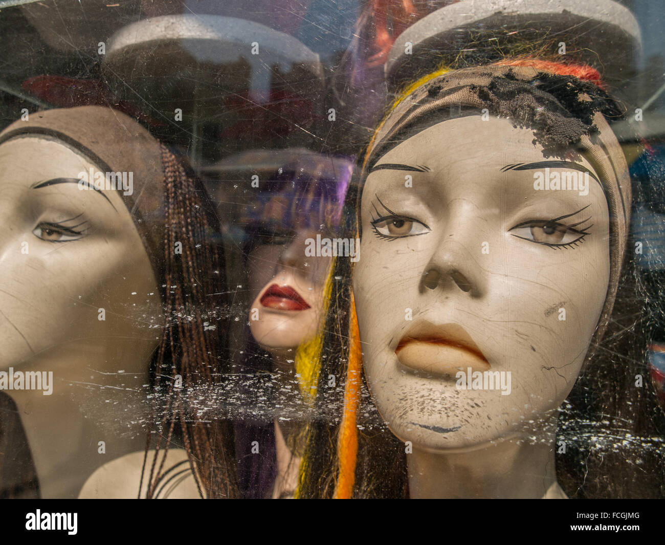 Three female caucasian mannequin heads wearing scarves with very serious expressions in a scratched up store front - Stock Image
