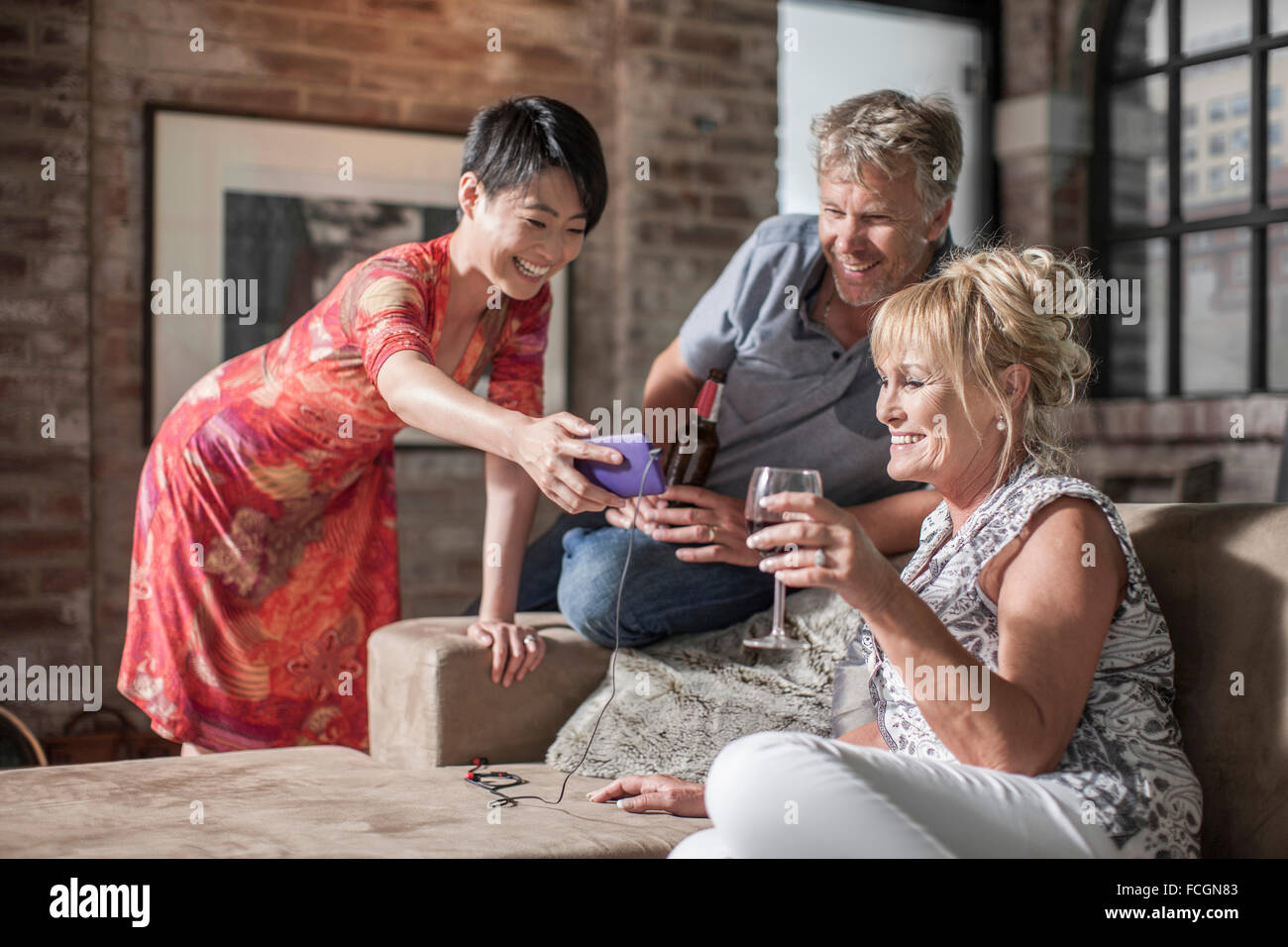 Friends together having a good time looking at cellphone - Stock Image