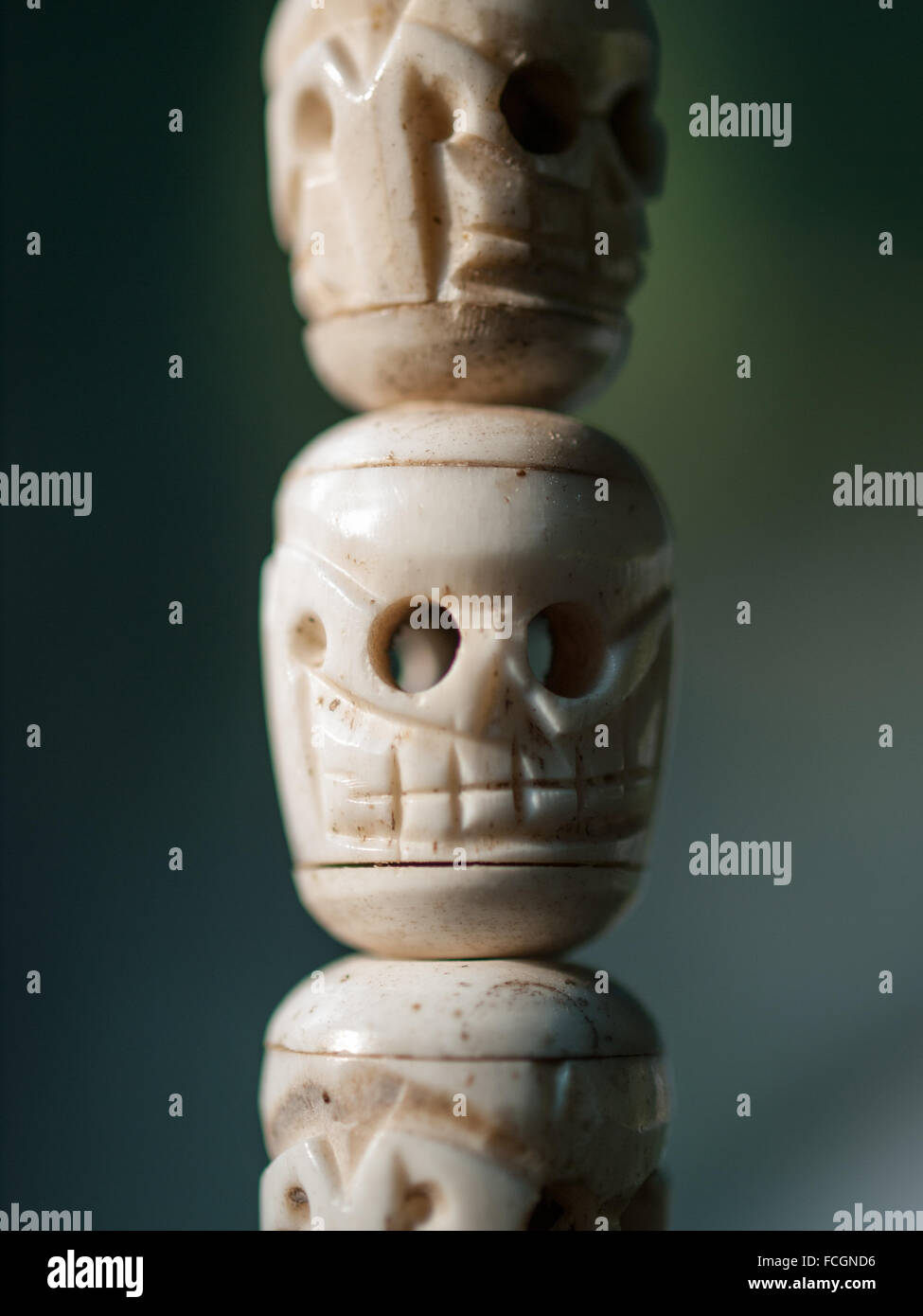 Primitive carving of three human skeletons hanging on string. - Stock Image