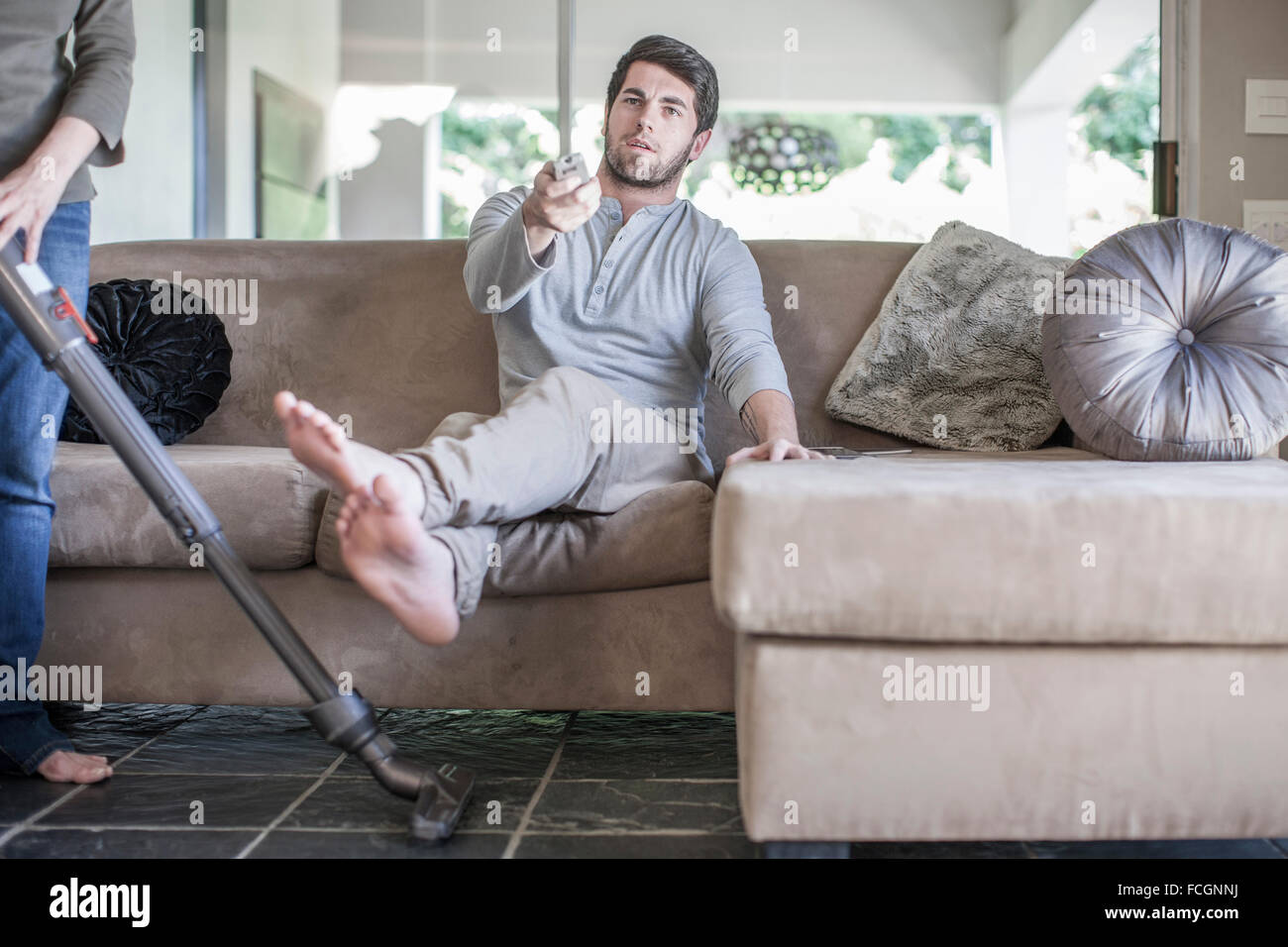 Woman Vacuum Cleaner And Man On Couch Tv Remote