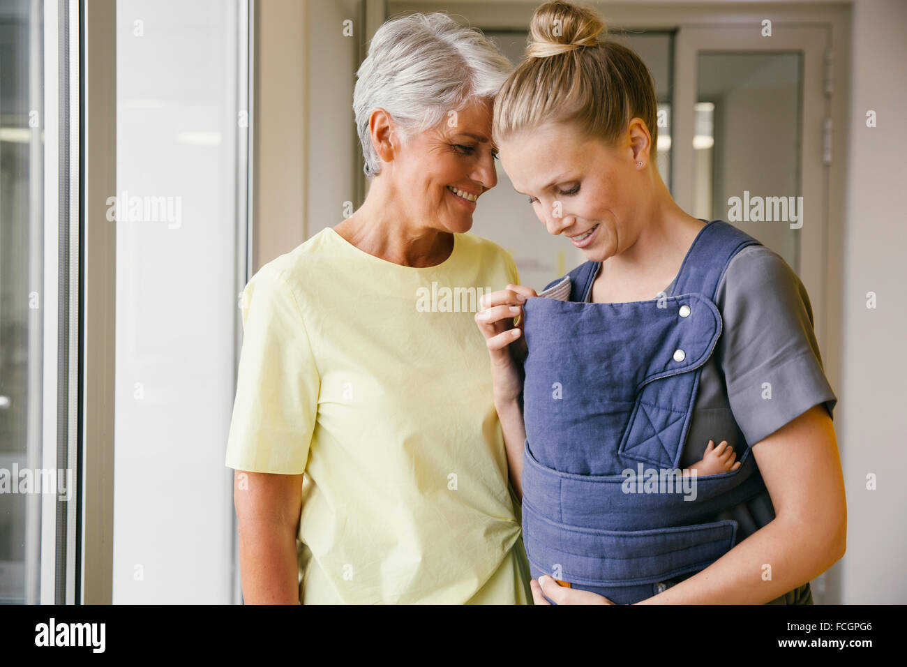 Young mother   baby carrier showing her baby to mature woman - Stock Image