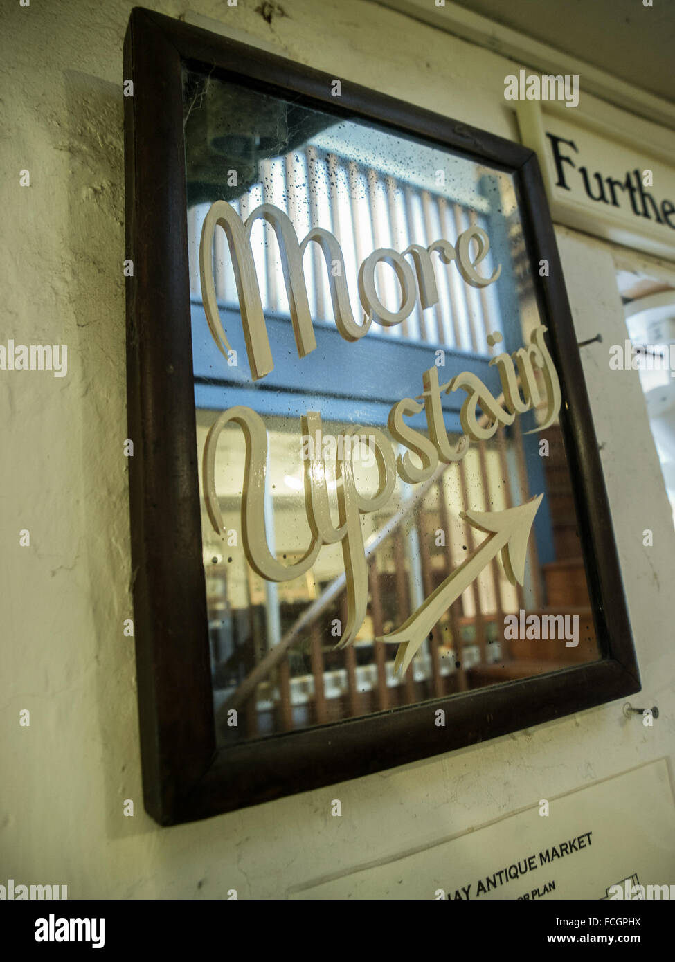 Brown wooden framed mirror with painted on cursive letters saying More Upstairs with arrow at an antique thrift - Stock Image