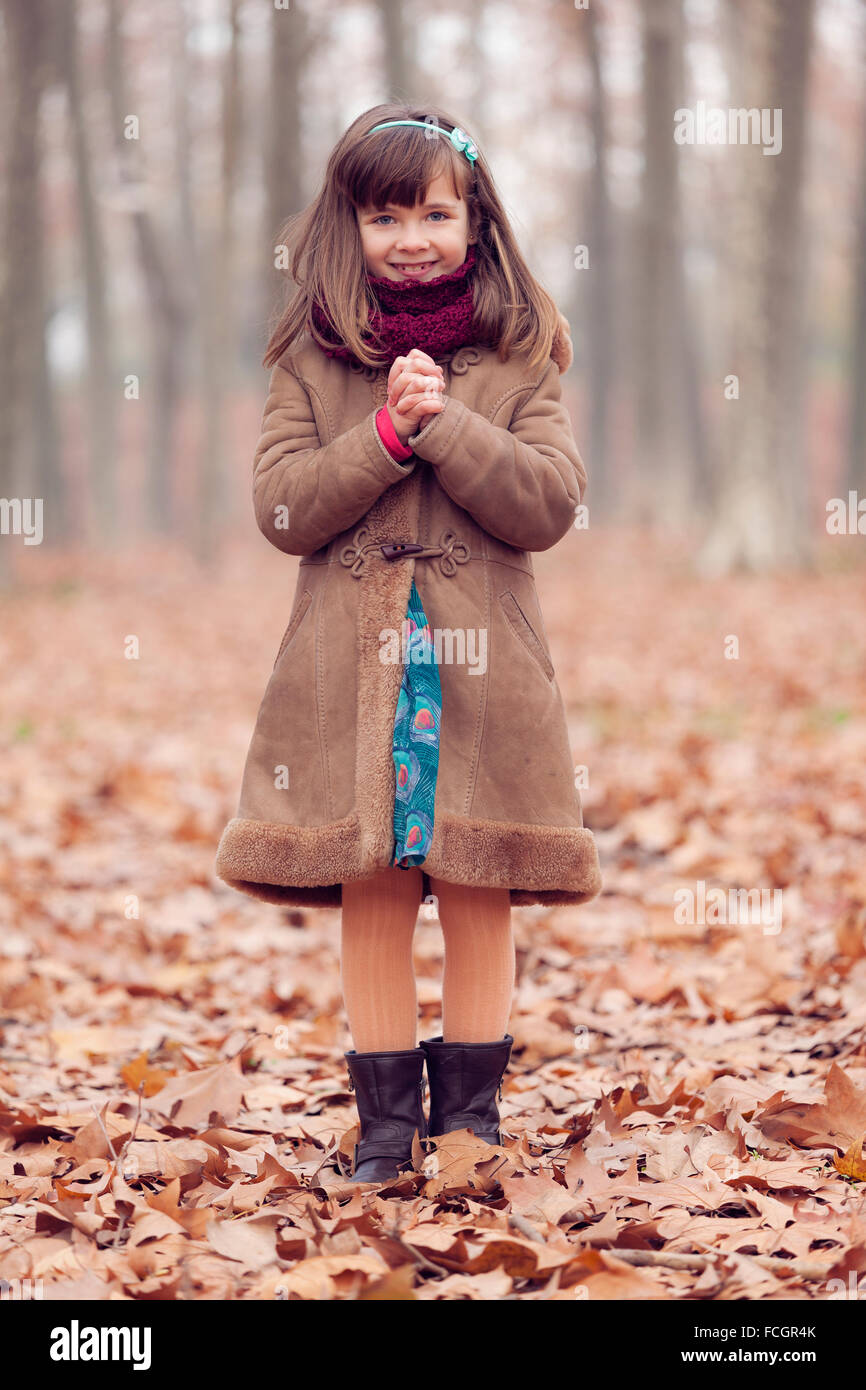 Young girl brown coat in park autum smiling hands folded - Stock Image