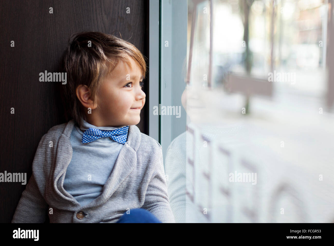 Portrait of smiling little boy   bow tie looking through window display - Stock Image