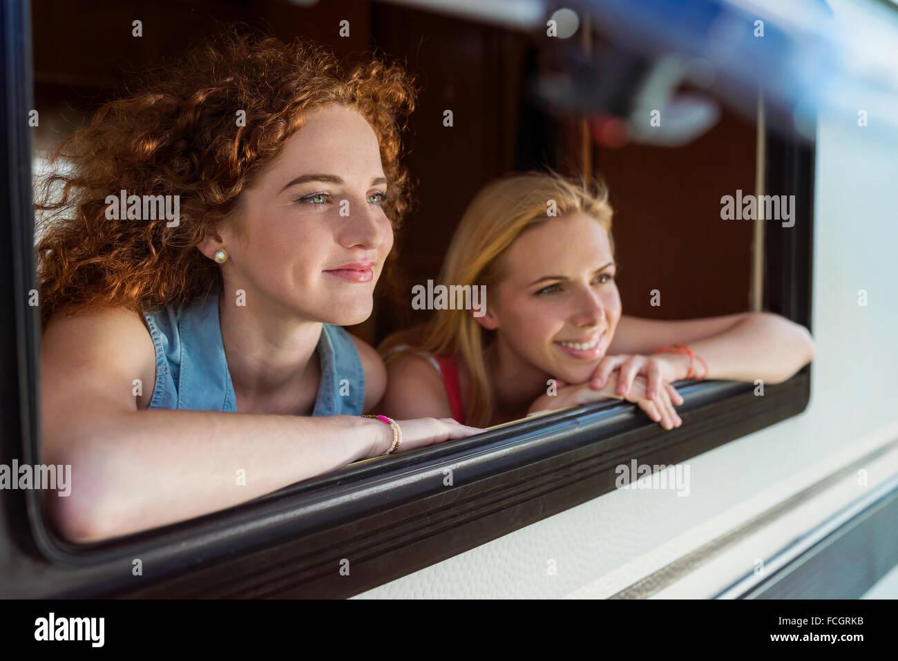 Two female friends looking through window of caravan watching something - Stock Image