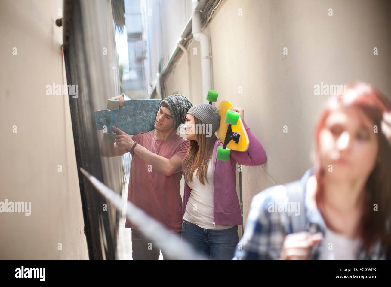 Friends   skateboards in a passageway - Stock Image