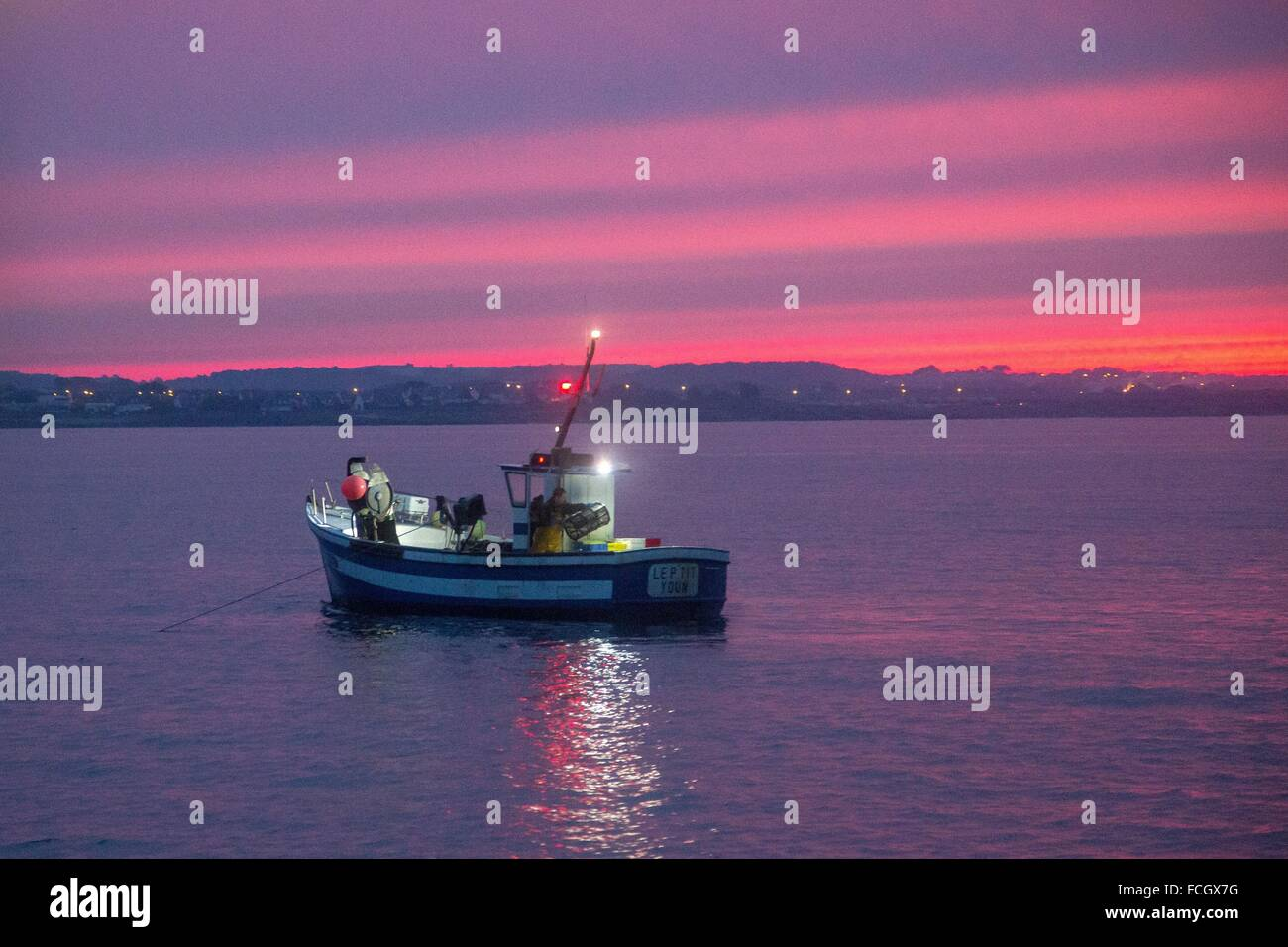 SHRIMP FISHER, FISHING AT SEA, SHRIMP TRAWLER AT DAWN OFF THE COAST OF LORIENT (56), BRITTANY, FRANCE Stock Photo