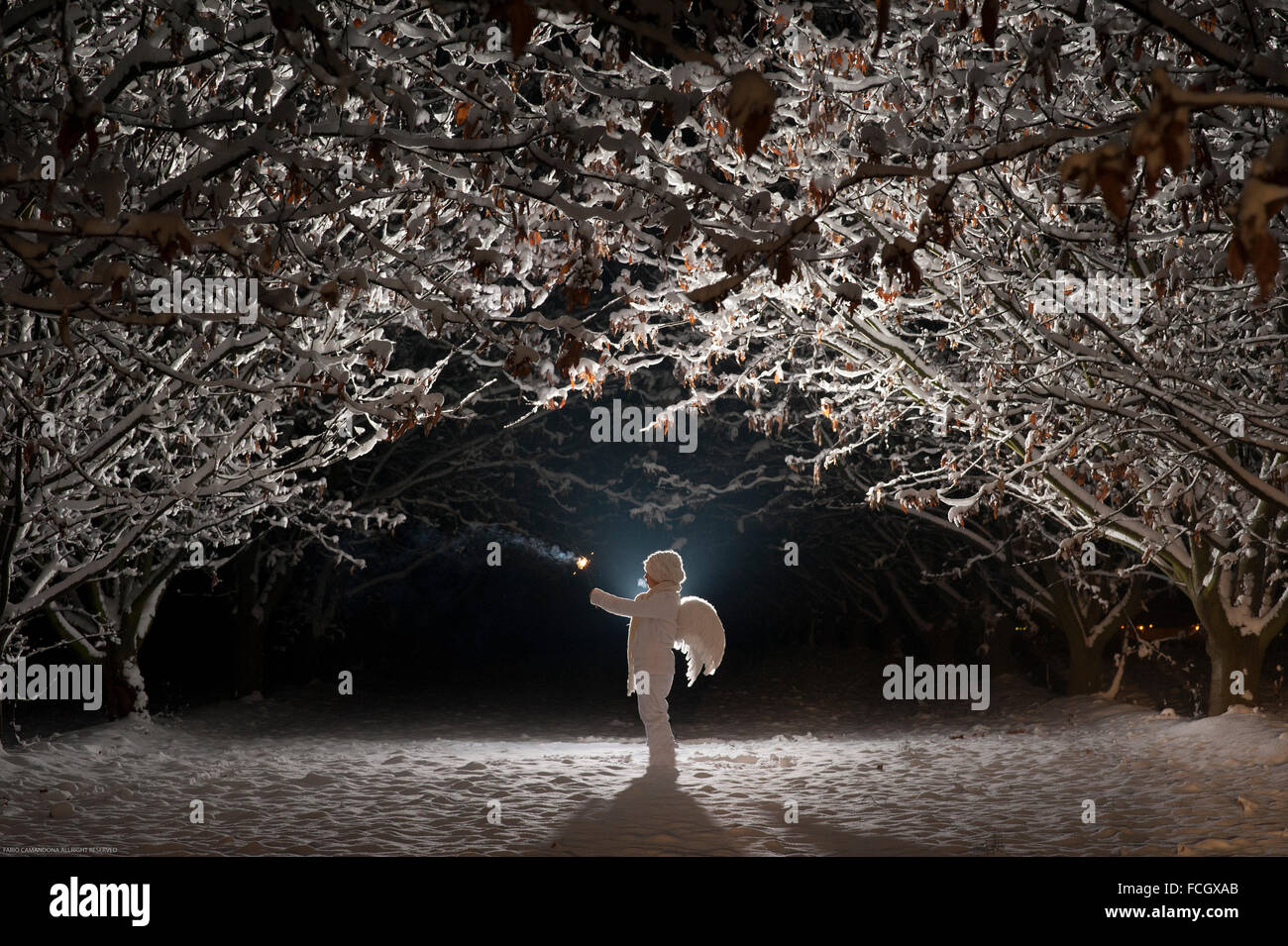 White dressed child   angel wings holding a light in cold winter's night - Stock Image