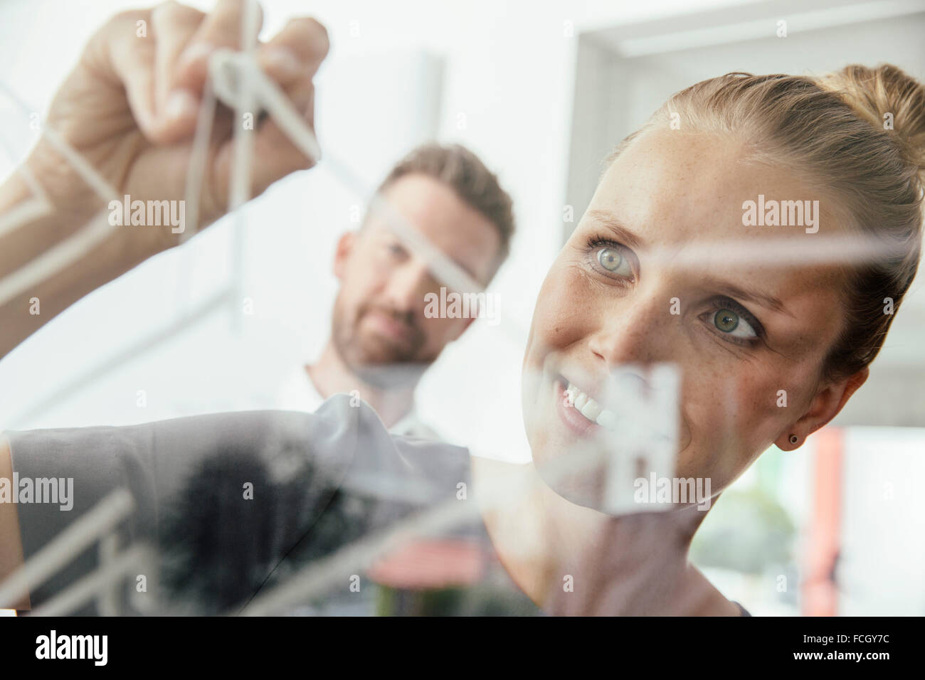 Young woman writing onto glass wall in office - Stock Image