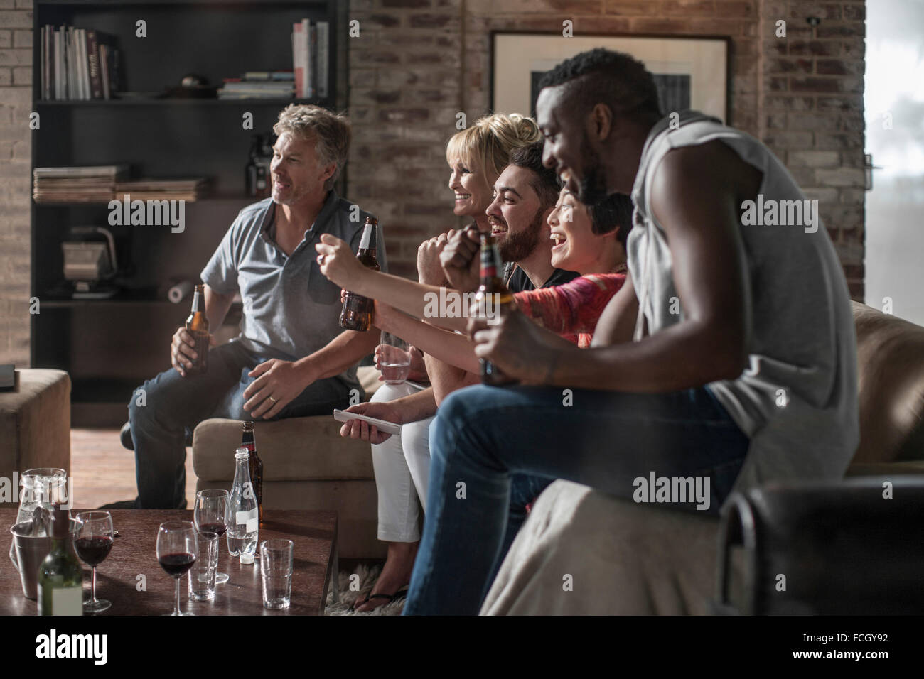 Friends together having a good time watching TV - Stock Image