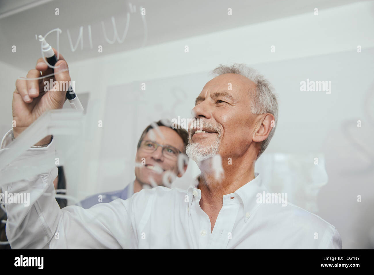 Two men writing onto glass wall in office - Stock Image