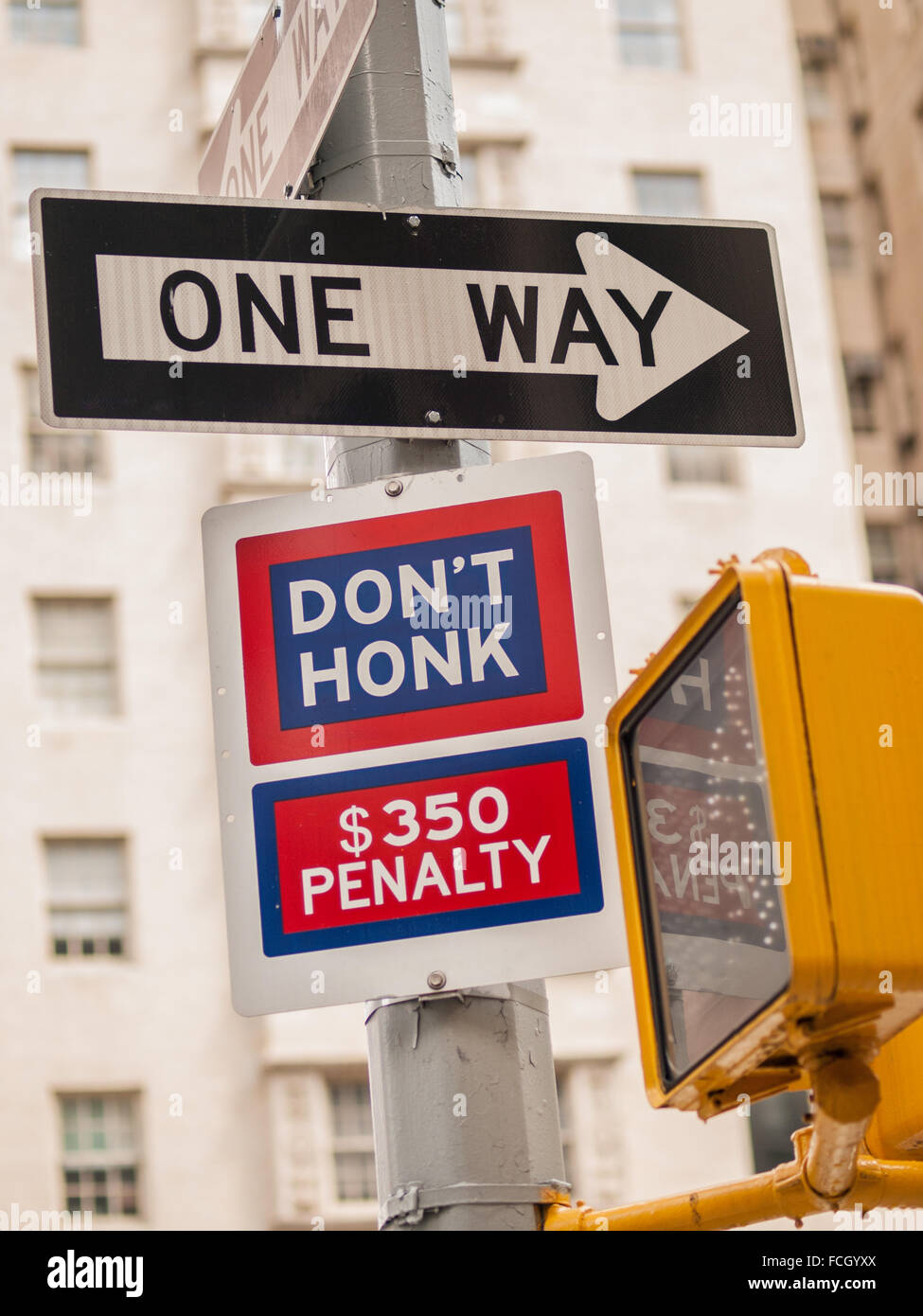 Black and white One Way sign and blue and red Don't Honk $350 Penalty sign at a crosswalk on a post in Manhattan, - Stock Image