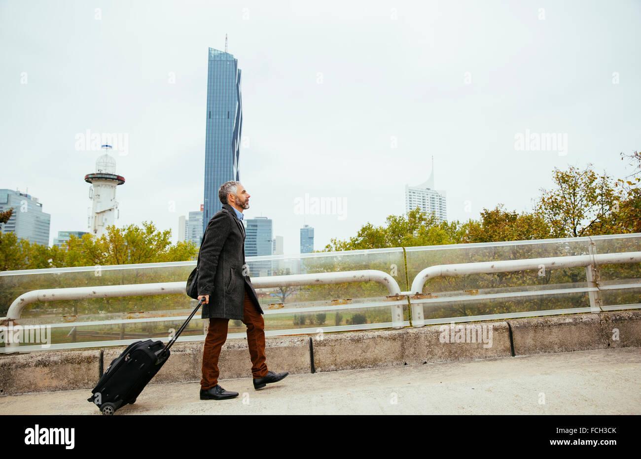 Austria Vienna businessman   baggage walking up Reichsbruecke - Stock Image