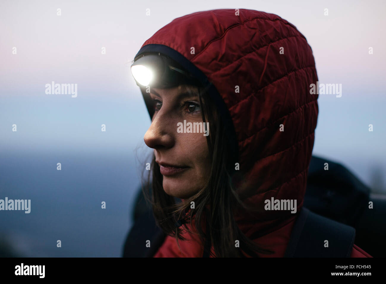 Female hiker wearing headlamp at twilight - Stock Image