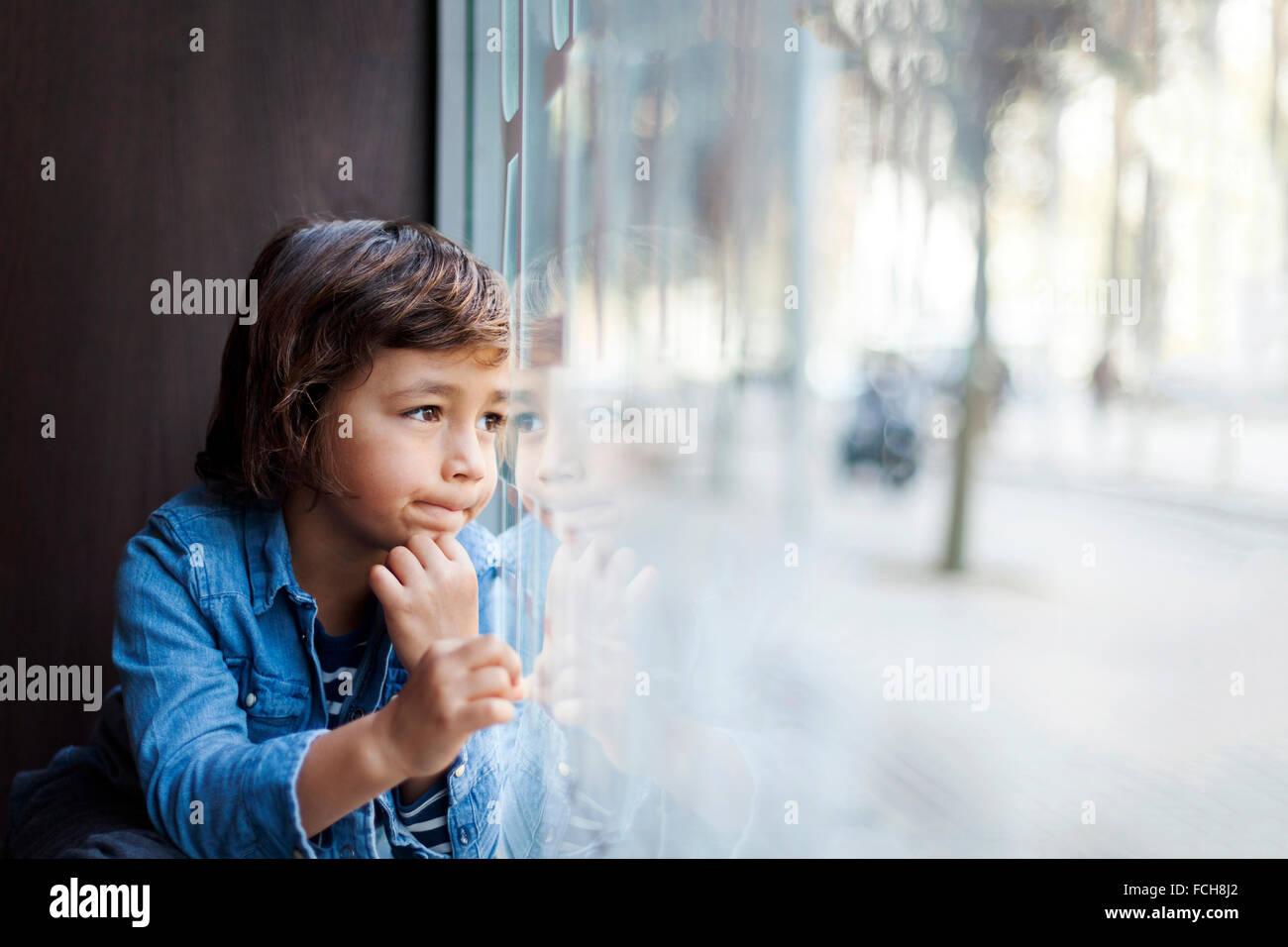 Portrait of little boy looking through window display - Stock Image