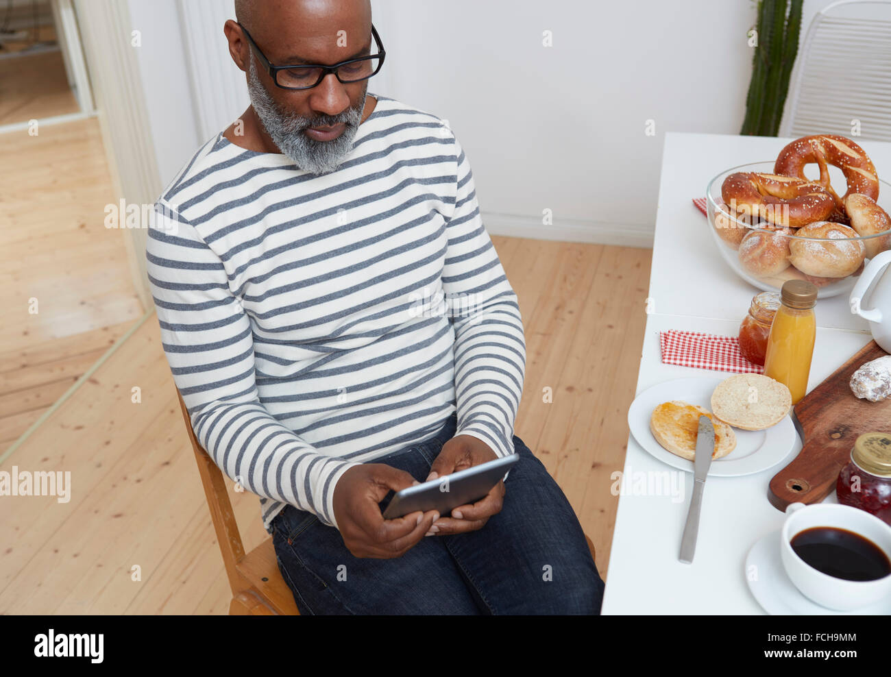 Man sitting at laid breakfast table using digital tablet - Stock Image