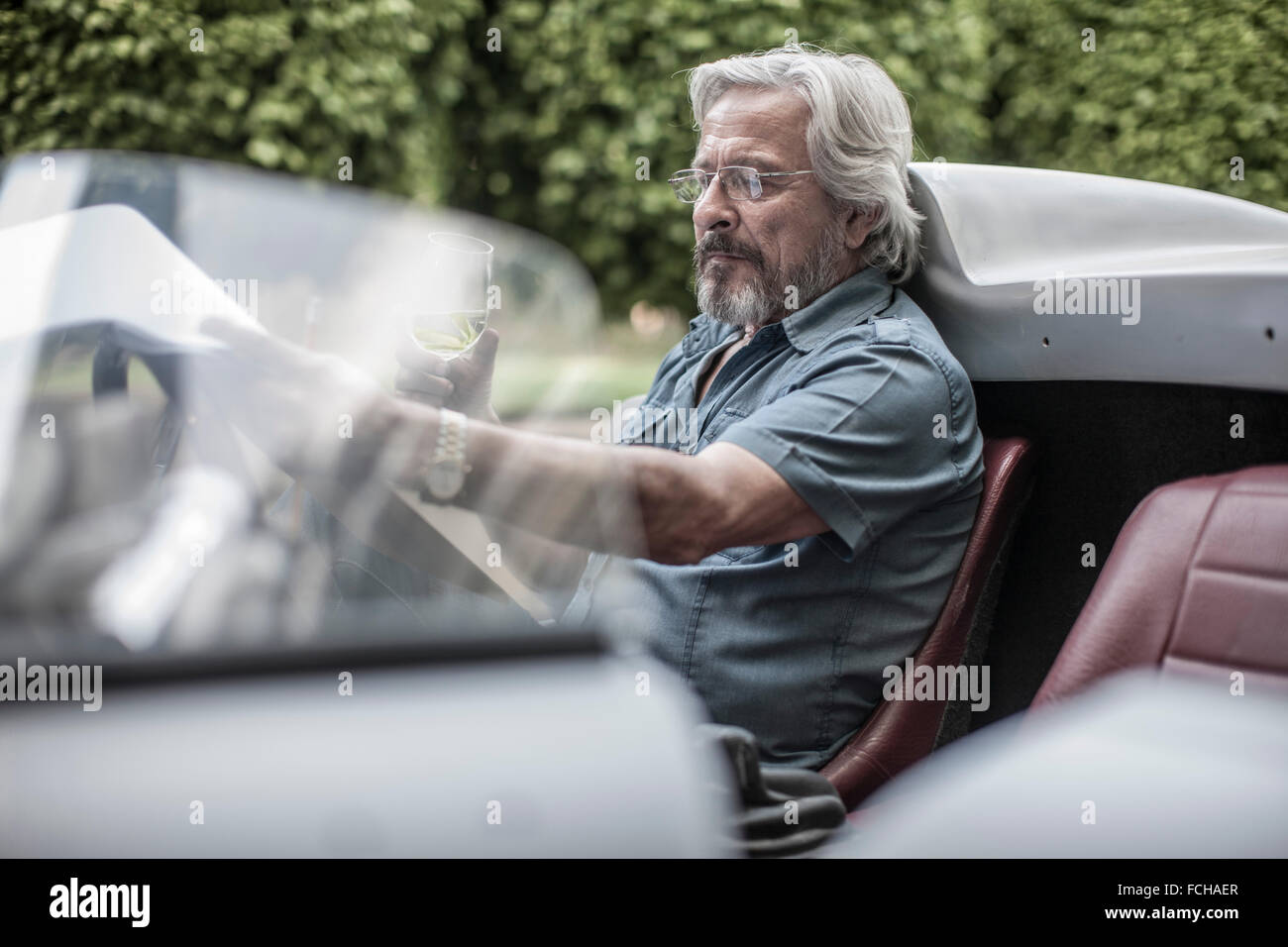 Senior man in sports car looking at check list drinking lemonade - Stock Image