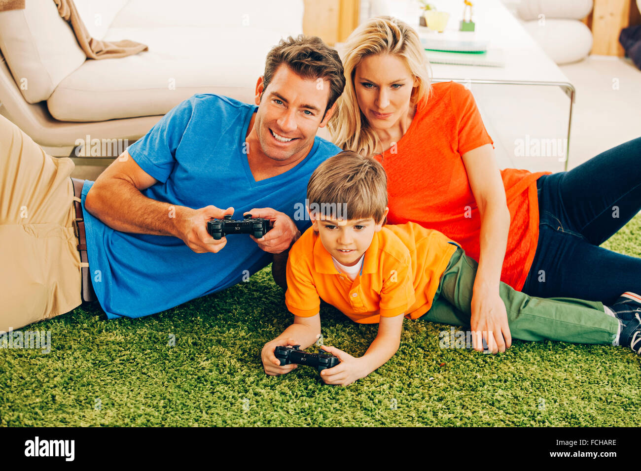 Family of three playing video game in living room - Stock Image