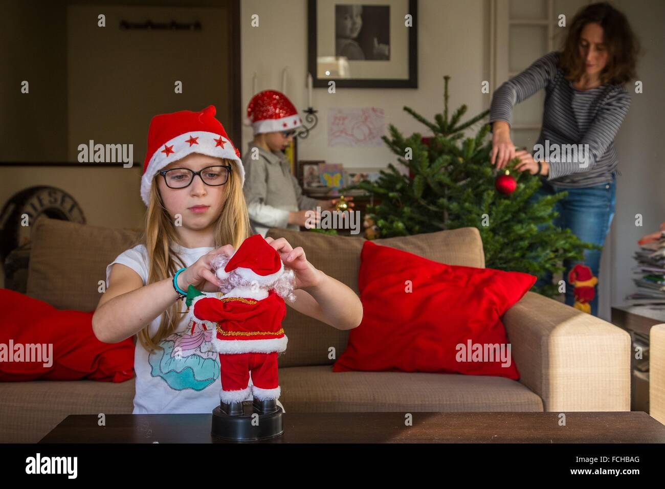 FAMILY DECORATING THE CHRISTMAS TREE - Stock Image