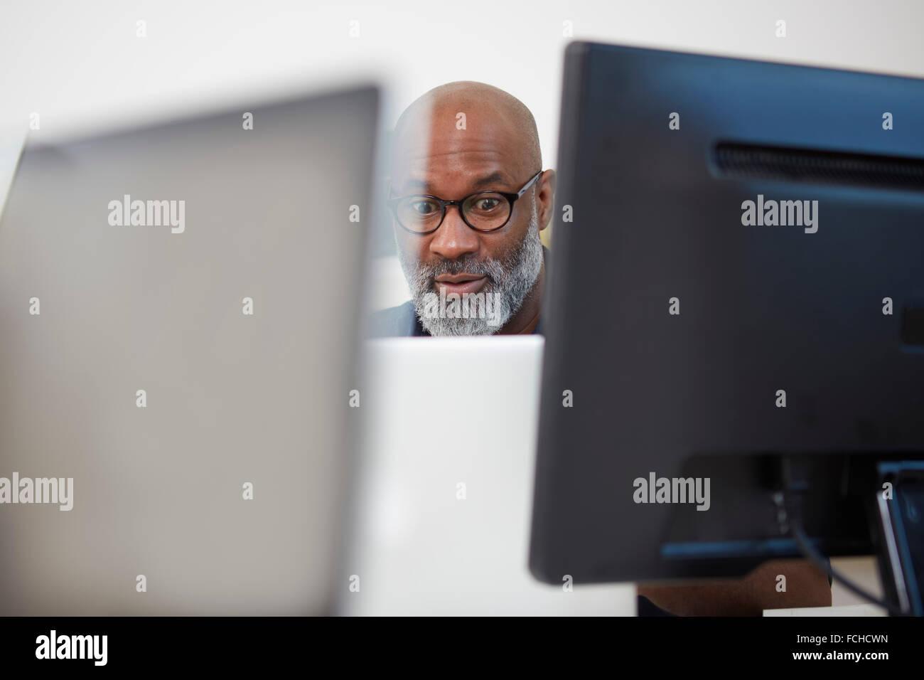 Portrait of astonished man between computer monitors - Stock Image