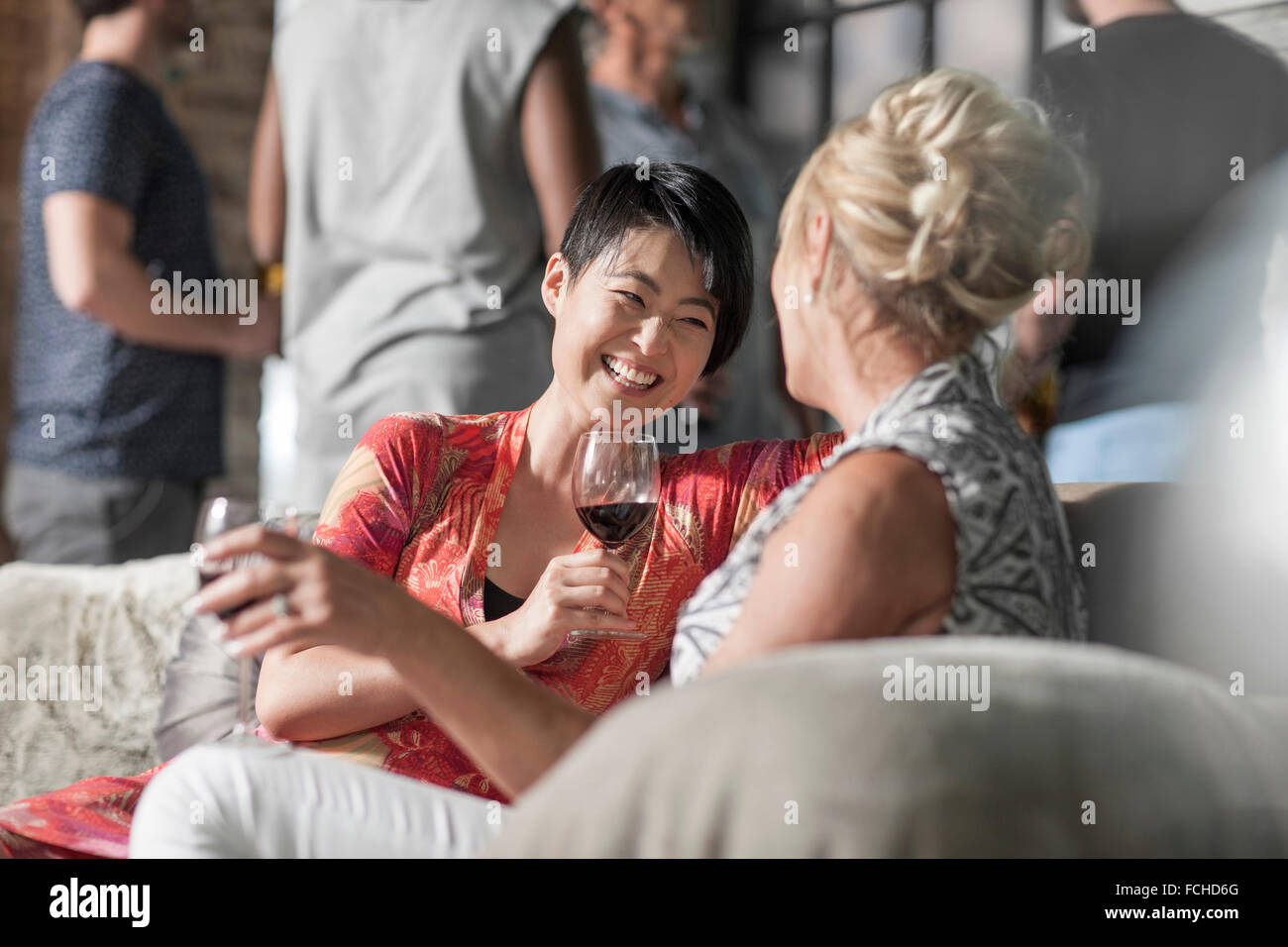 Friends together having a good time sitting on couch chatting - Stock Image