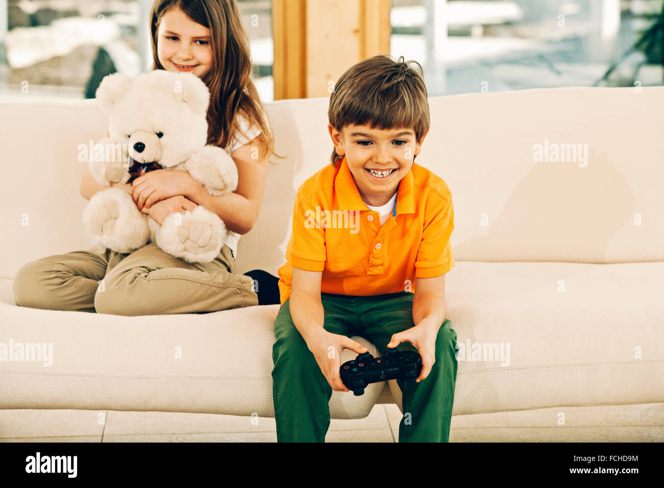 Boy playing video game in living room   sister holding teddy bear - Stock Image