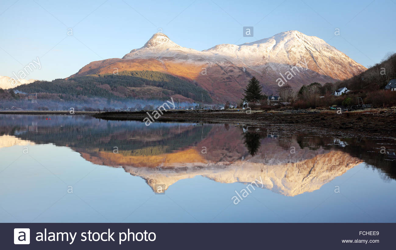 The snow covered pap of Glencoe (Sgorr na Ciche) reflecting on a perfectly calm Loch Leven. - Stock Image
