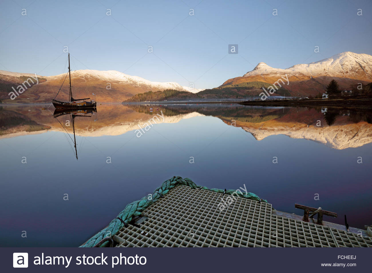 From a jetty on Loch Leven the snow covered pap of Glencoe (Sgorr na Ciche) and boat reflects on a perfectly calm - Stock Image