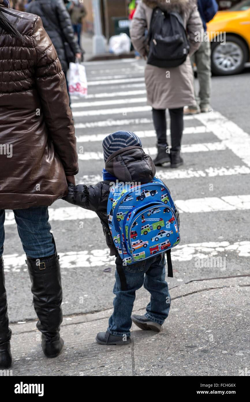 Little Boy, 2-3 years old, holding his Mother´s hand, waiting to safely cross a New York City Street. - Stock Image