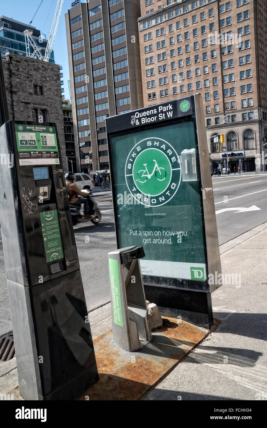 Bike Share Toronto Station at Queens Park and Bloor Street West, along with a vending machine for renting the bikes. - Stock Image