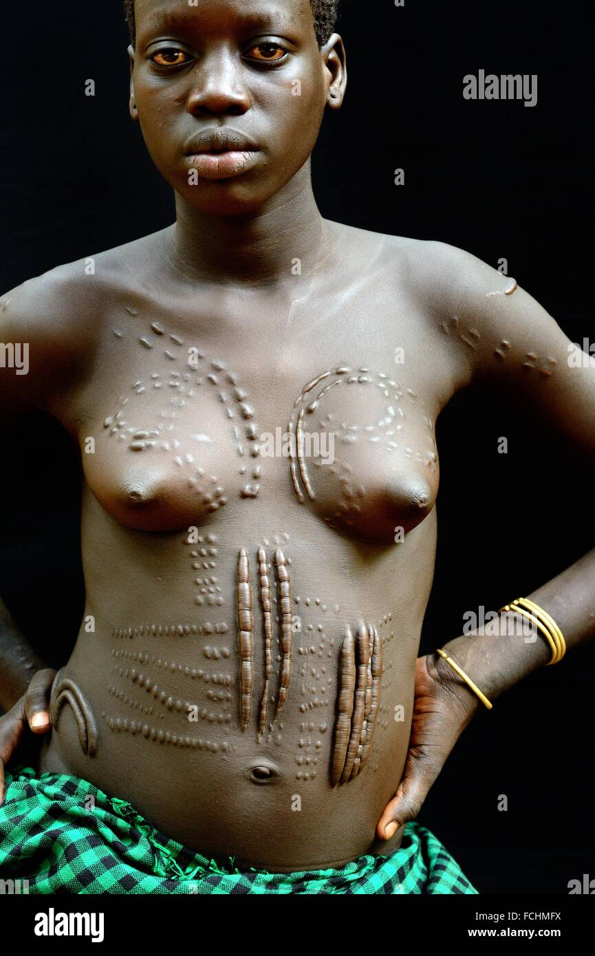 Young woman from the Bodi tribe displaying elaborate scarifications - for purely aesthetic purpose - on her body, Stock Photo
