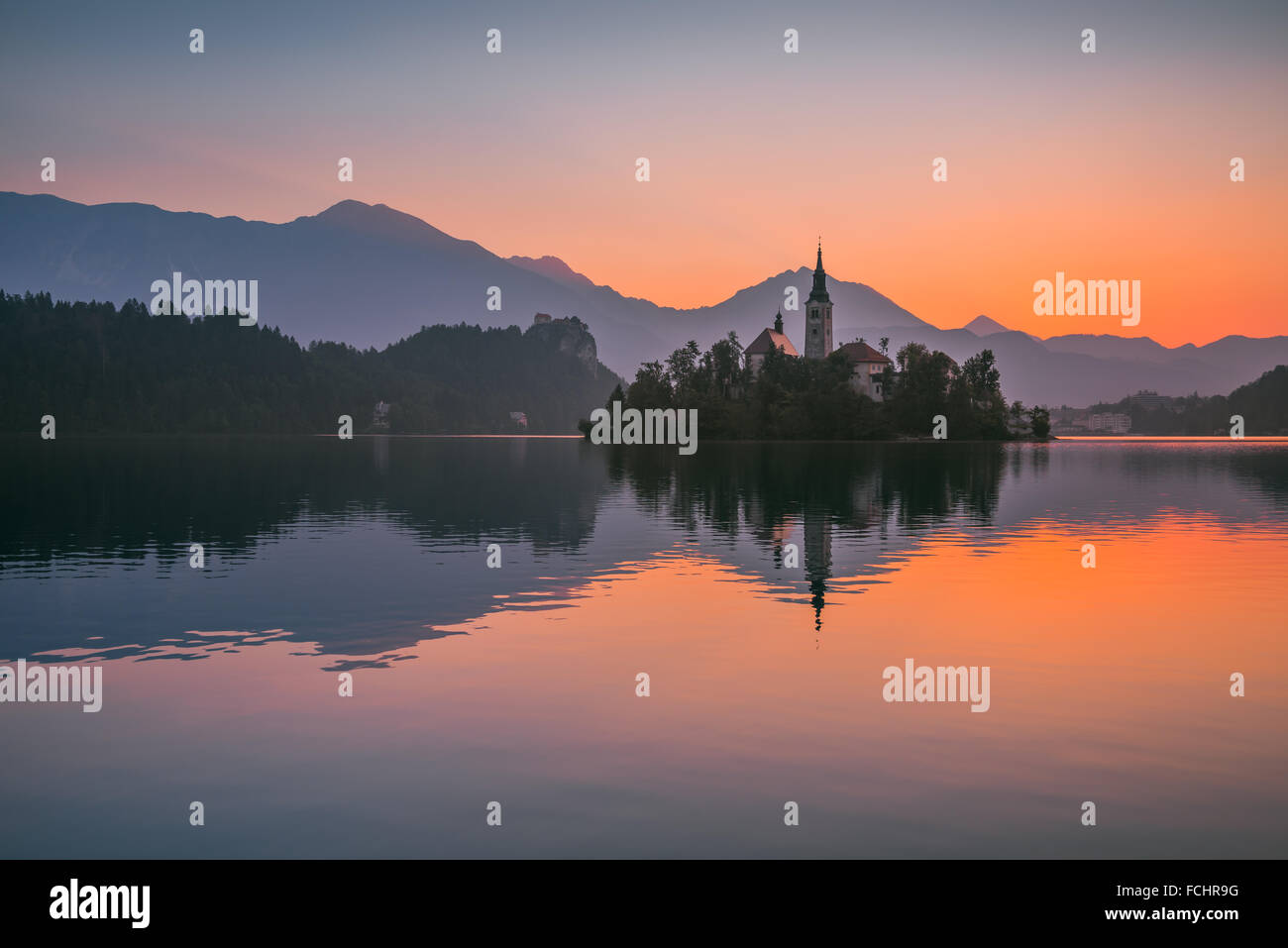 Little Island with Catholic Church in Bled Lake, Slovenia at Sunrise with Castle and Mountains in Background - Stock Image