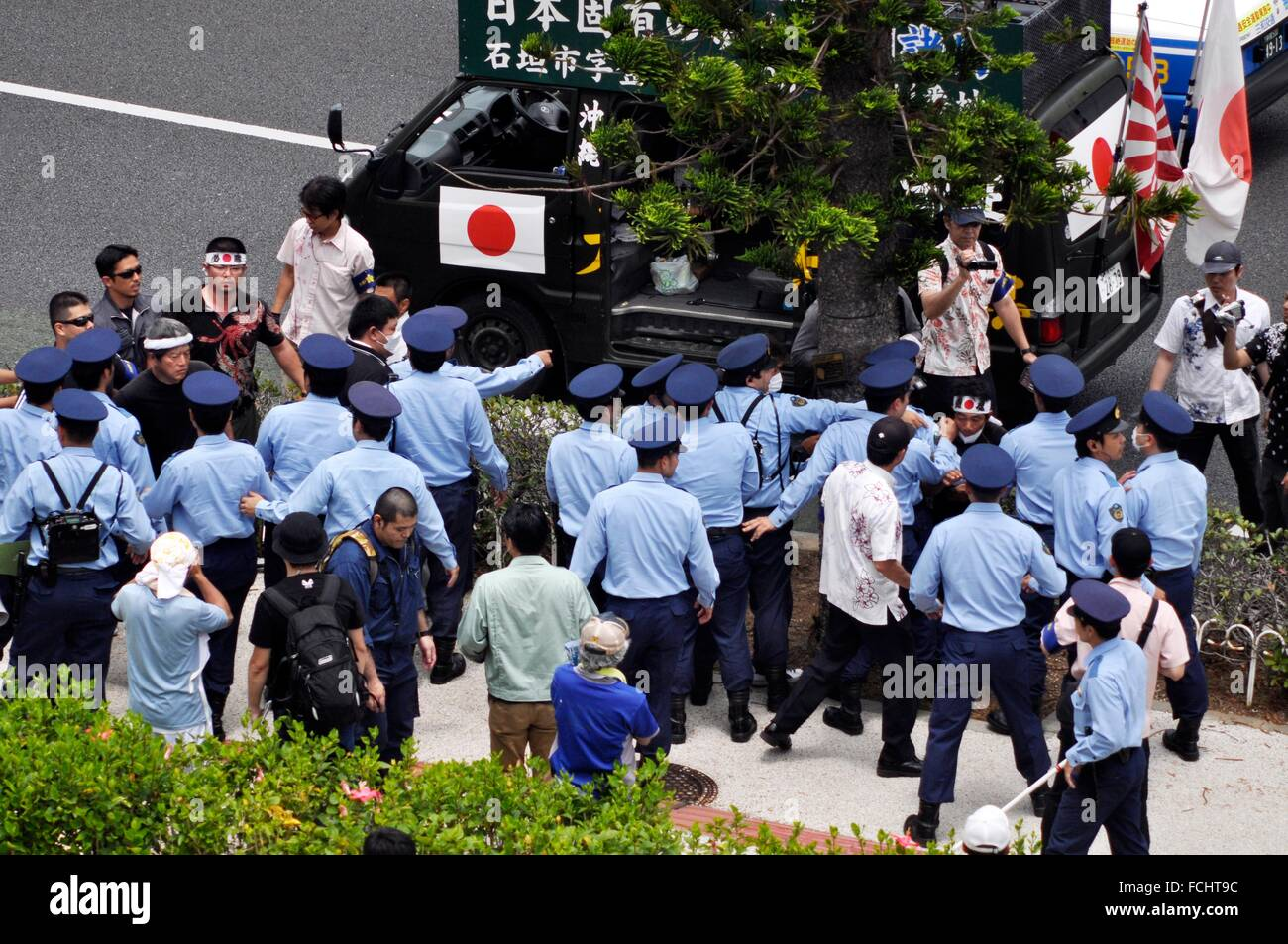Naha, Okinawa, Japan: Japanese ultra-nationalists attacking pacifists by the Okinawa Cellular Stadium during the - Stock Image