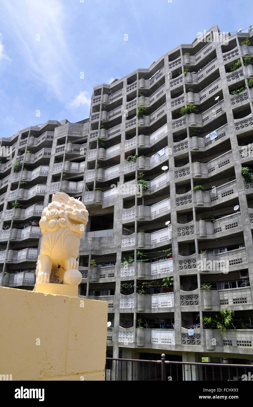 Naha, Okinawa, Japan: a Shisa on a grave of a cemetery by a huge condo in Aja, Shisa is a traditional Ryukyuan decoration, - Stock Image