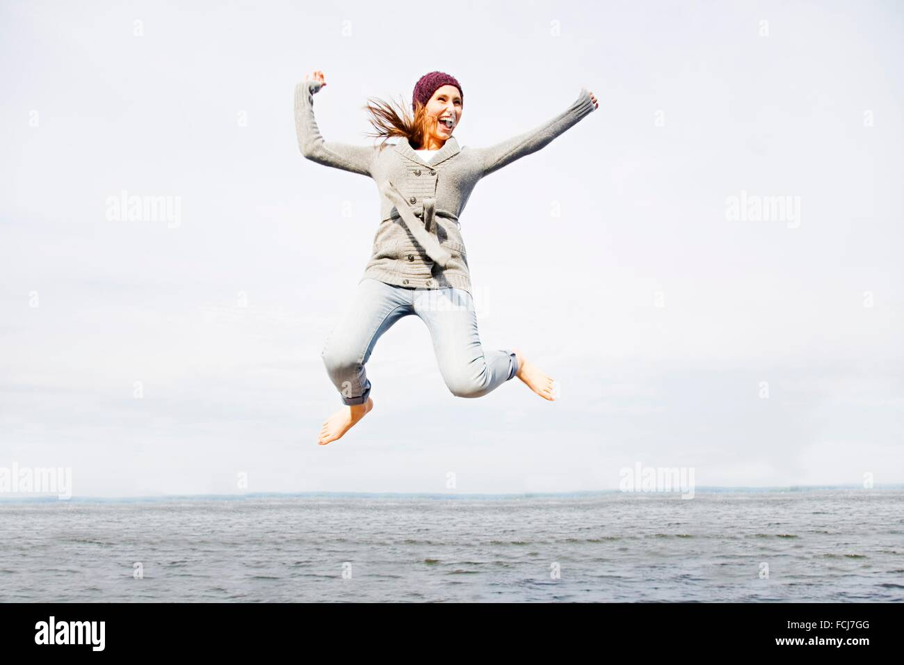 Young woman radiant with happiness jumping by the sea - Stock Image