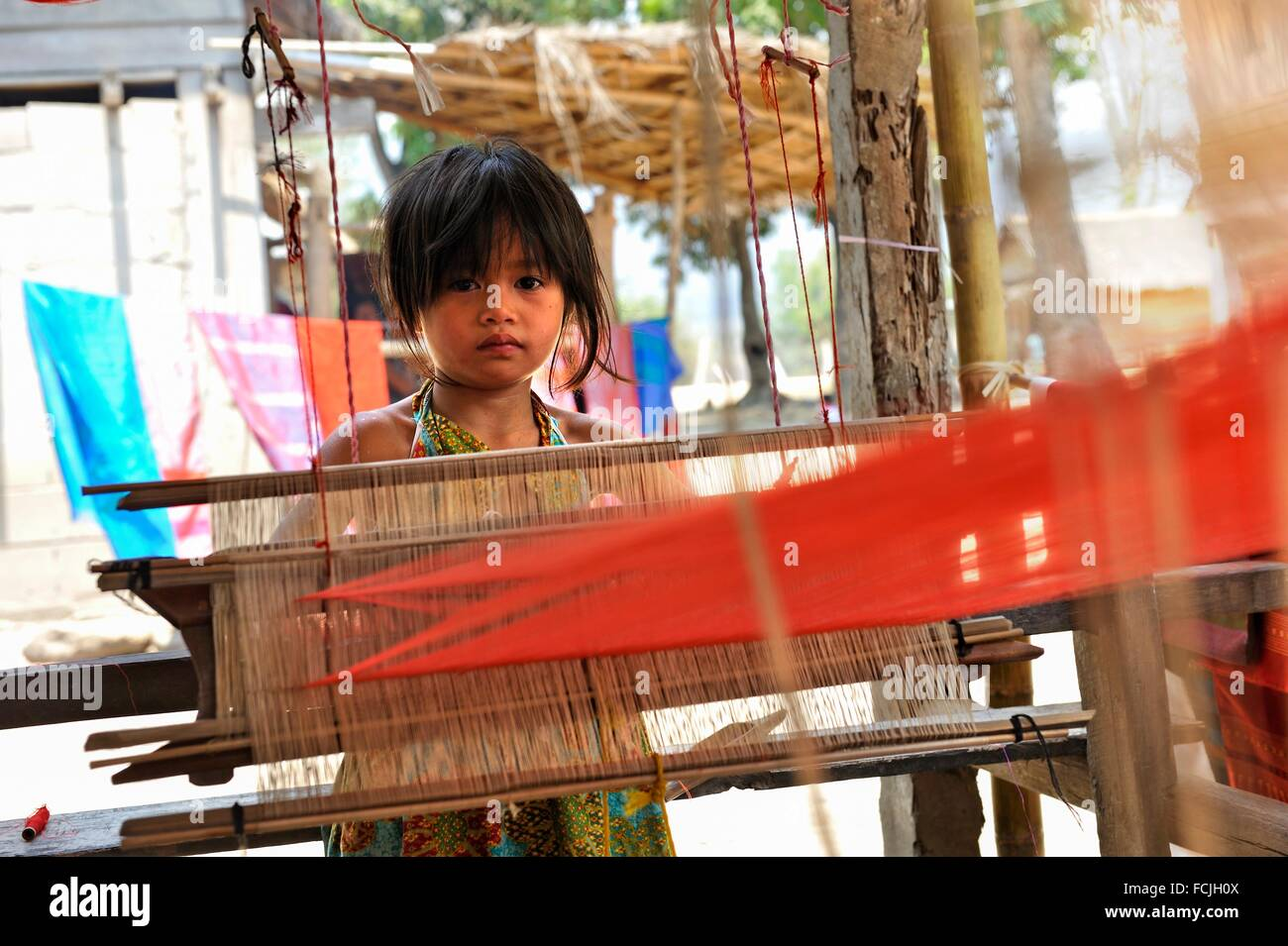little girl beside a weaving loom at Ban Baw, a traditional Lao Loum village between Luang Prabang and Pakbeng, - Stock Image