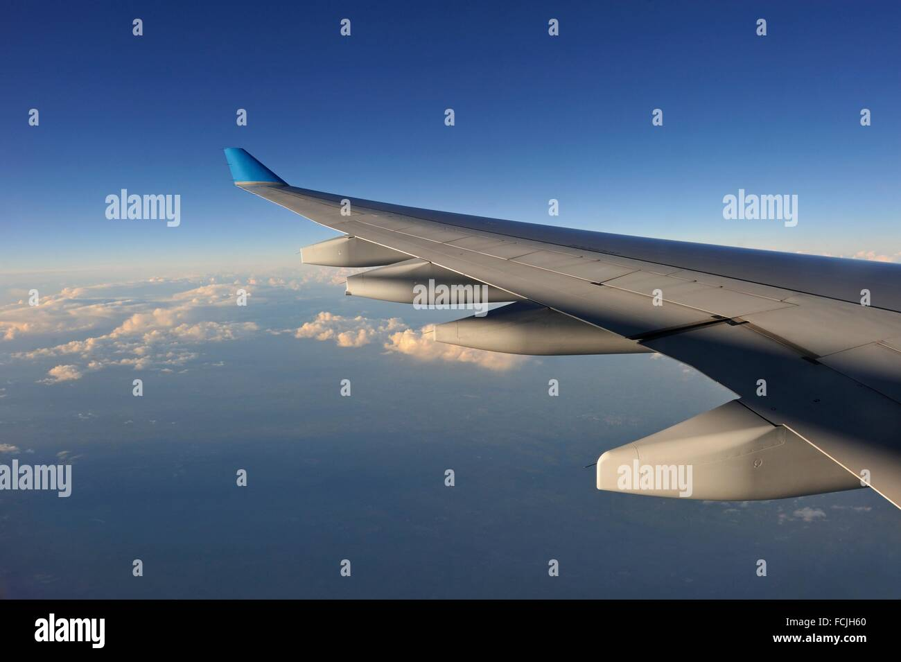 in-flight airliner wing seen through the window. - Stock Image