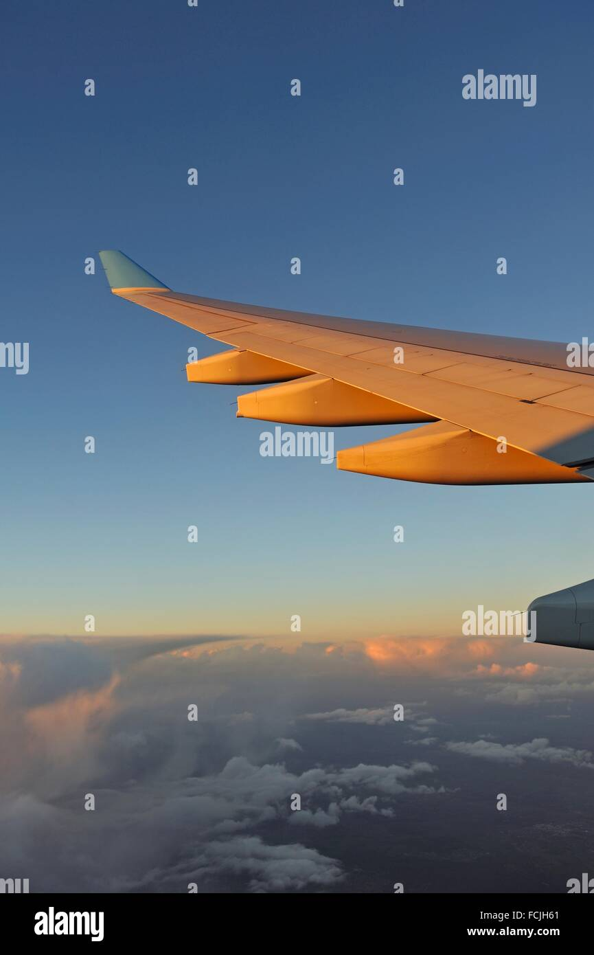 in-flight airliner wing seen through the window at sunset. - Stock Image