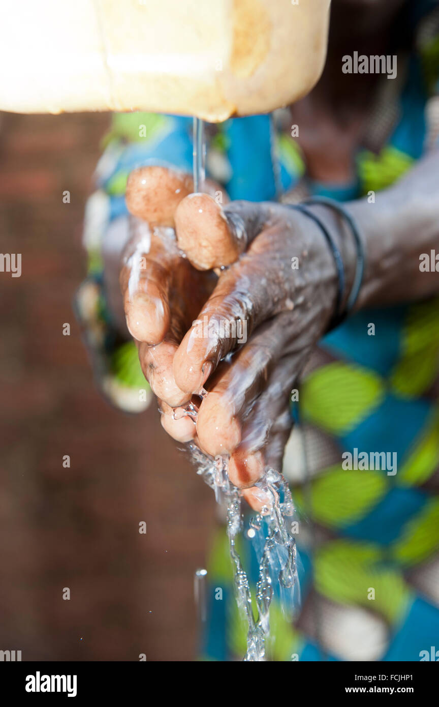 Lady washing hands from a 'Tip Tap' an efficent way to clean hands without wasting water. Uganda. - Stock Image