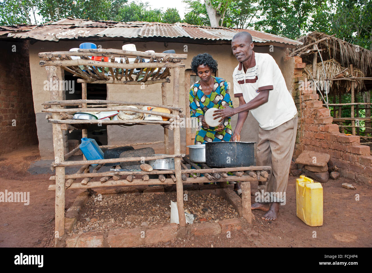 Ugandan couple working together to clean dishes in a rural village. Uganda. - Stock Image